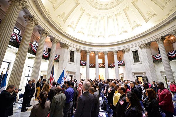 2014年5月22日,美國國土安全部長約翰遜(Jeh Johnson)帶領移民在位於紐約華爾街的聯邦國家紀念堂(Federal Hall National Memorial)宣誓入籍。這75名移民來自世界31個國家,這一天,他們都成為了美國人,為此感到驕傲和自豪。(戴兵/大紀元)