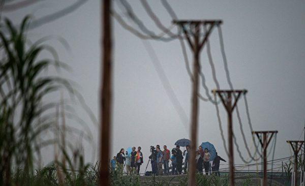6月2日,媒體記者在岸邊遠遠的觀望「東方之星」救援工作進展情況。(JOHANNES EISELE/AFP)