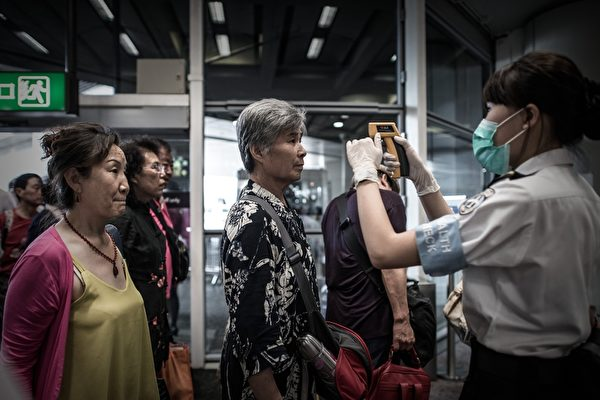 2015年6月5日,香港机场对乘客们进对中东呼吸综合症(MERS)的检查措施。近日韩国报告了一个受感染的医生造成了上千名需隔离的观察者。(PHILIPPE LOPEZ/AFP/Getty Images)