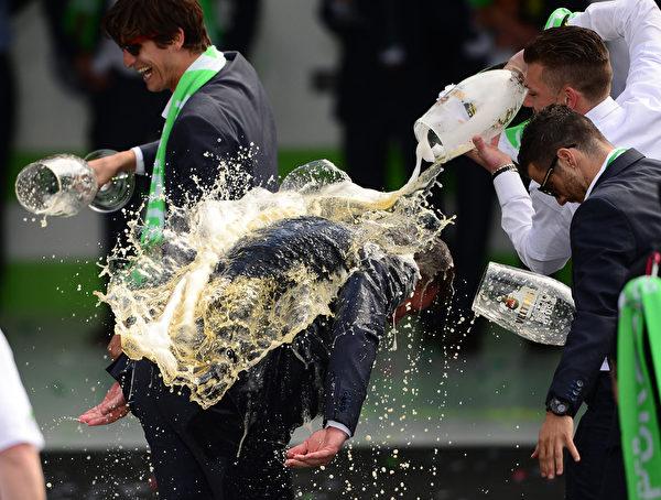 2015年5月31日,沃尔夫斯堡足球队的主教练迪特·黑金(中)在庆祝活动中被他的球员以啤酒淋身,该队前一晚赢得了德国足协杯DFB Pokal足球决赛冠军。(ETER STEFFEN/AFP)