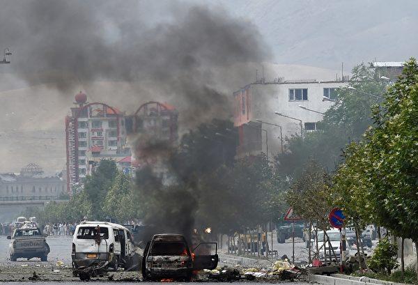 2015年6月22日,喀布尔,阿富汗议会大厦前一辆被塔利班武装分子袭击的汽车遭焚烧,所幸所有国会议员已安全疏散。 (SHAH MARAI/AFP/Getty Images)