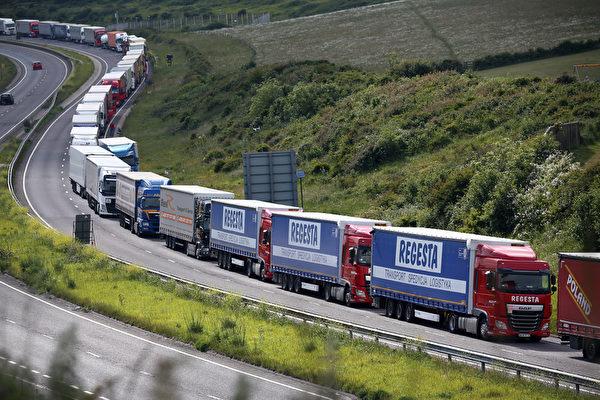 2015年6月23日,英国多佛,从伦敦前往英吉利海峡隧道口的M20公路上,停靠着一排排的大卡车。码头工人的罢工行为导致英吉利海峡隧道口和渡轮码头暂停运营。(Carl Court/Getty Images)