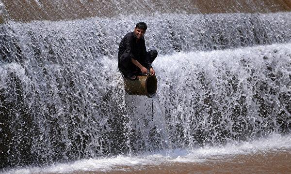 2015年6月22日,一名巴基斯坦青年在伊斯兰堡郊外河边避暑。热浪在巴基斯坦已造成至少122人死亡,南部港口城市卡拉奇6月20日温度高达45摄氏度(111华氏度),逼近1979年6月创下的最高温47℃。(Aamir QURESHI/AFP)