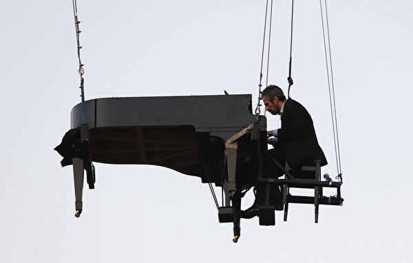 """2015年6月21日,在巴西圣保罗一年一度的""""Virada文化""""活动中,巴西钢琴家里卡多·德·卡斯特罗·蒙泰罗在以线悬吊在空中的钢琴上弹奏。""""Virada文化""""是在城区提供24小时不间断的文化派对,如音乐,舞蹈,烹饪,戏剧,艺术和历史等形式表达的展览。(Miguel SCHINCARIOL/AFP)"""