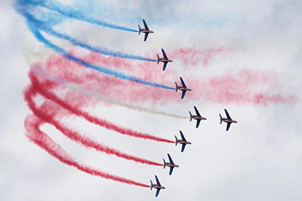"""2015年6月21日,来自法国的精英飞行队""""法兰西巡逻兵""""(PAF)飞机在巴黎国际航展飞行中释放法国国旗颜色的烟雾。(ERIC PIERMONT/AFP)"""