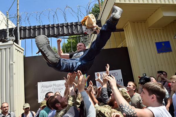2015年6月23日,乌克兰队和第54独立侦察排参加东乌克兰对抗恐怖分子的前指挥官前中尉,25岁的丹尼斯·舒克从基辅监狱中保释后,被庆贺的人高高抛起。(SERGEI SUPINSKY/AFP)