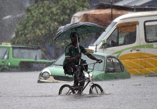 2015年6月22日,科特迪瓦阿比让,一名男子在大雨中骑着自行车,本月的高降雨量已造成至少16人死亡。(SIA KAMBOU/AFP)