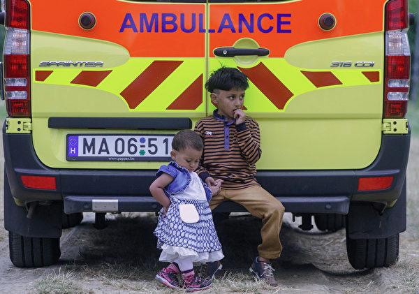 2015年6月24日,在匈牙利塞格德附近,当地警方在塞尔维亚边界上巡逻时,2名儿童坐在救护车上等待。匈牙利表示,因不堪重负,已无限期暂停欧盟庇护政策。(CSABA SEGESVARI/AFP)