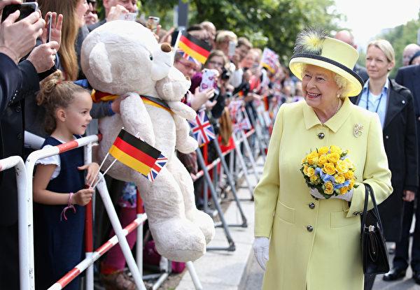 2015年6月26日,德国柏林,英国女王伊丽莎白二世对一个带着大型熊布偶的儿童微笑着。当天为女王在德国国事访问的最后一天。(Chris Jackson/ Getty Images)