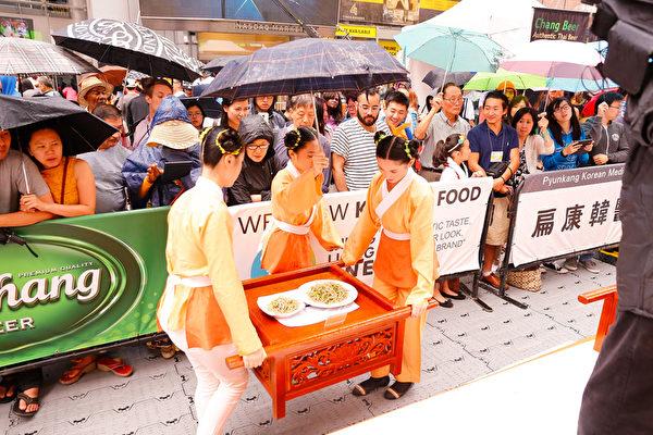 6月27日,第七屆新唐人全世界中國菜廚技大賽決賽在紐約時代廣場舉行。當天下午下起了雨,觀眾打傘觀看比賽,不願離去。(戴兵/大紀元)