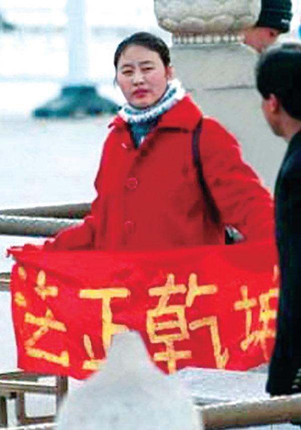 2001年,一名女法轮功学员在天安门广场和平请愿,诉说法轮大法好。面对邪恶至极的打压迫害,16年来法轮功学员不曾停止过对世人诉说事实真相。(明慧网)