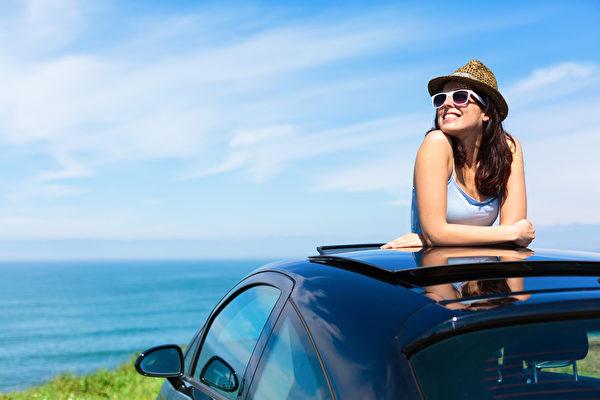 輕鬆快樂的女人在夏季旅遊度假海岸倚在汽車天窗與背景的大海。(fotolia)