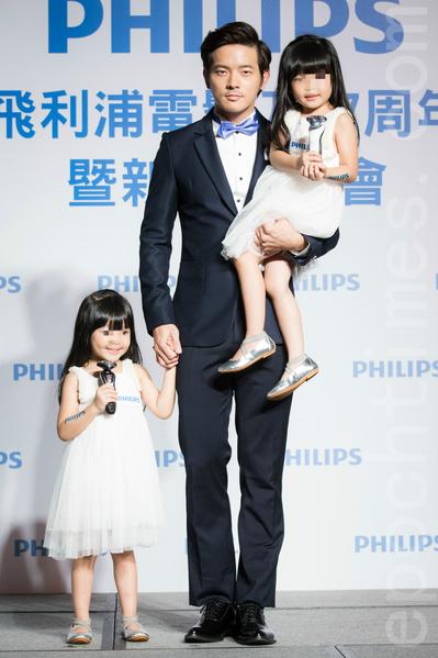 艺人宥胜(中)7月7日在台北出席代言活动,并和可爱的双胞胎一起展演。(陈柏州/大纪元)