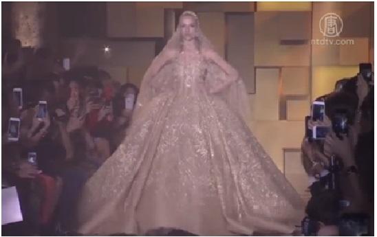 Elie Saab金色新娘礼服,华丽高贵的就像是童话故事中的皇后再现,也因此成为了瞩目焦点。(新唐人视频截图)