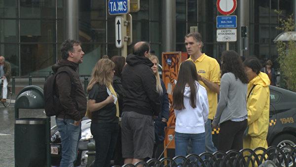 比利時法輪功學員在位於布魯塞爾市區的歐洲議會大樓前舉辦活動。法輪功學員在向民眾講真相。(大紀元)
