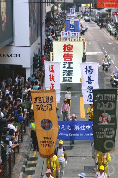 """2015年7月18日,香港法轮功学员开始一连两天举行纪念7·20活动,首日约700名学员在九龙区闹市举行""""控告江泽民""""大游行,吸引许多市民及大陆游客的观看。(潘在殊/大纪元)"""