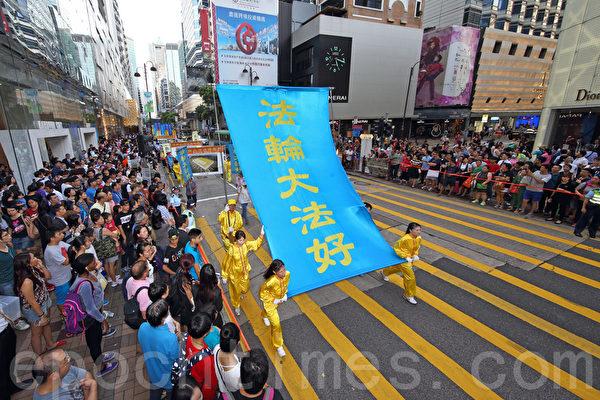 """香港法轮功学员7月18日开始一连两天举行纪念7·20活动,首日约700名学员在九龙区闹市举行""""控告江泽民""""大游行,吸引许多市民及大陆游客的观看。(潘在殊/大纪元)"""