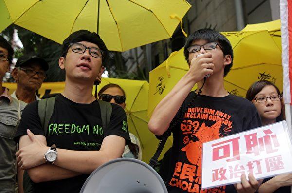 2015年7月14日,遭警方起诉的香港学民思潮召集人黄之锋及学联秘书长罗冠聪在香港西区警署外接受记者采访。黄之锋等人对于去年6月在中联办外面抗议期间阻碍警察的指控表示不认罪。(Isaac Lawrence/AFP/Getty Images)