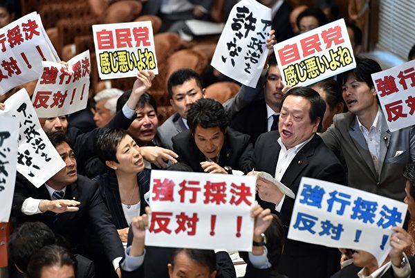 日本东京,攸关解禁日本集体自卫权的安保法案,7月16日在众议院进行全院表决,反对的议员举标语抗议。安保法案根据新的宪法解释,即使日本没有遭受直接攻击,只要发生日本的存立遭受威胁的事态(存立危机事态),也允许行使集体自卫权。(Yoshikazu TSUNO/AFP)