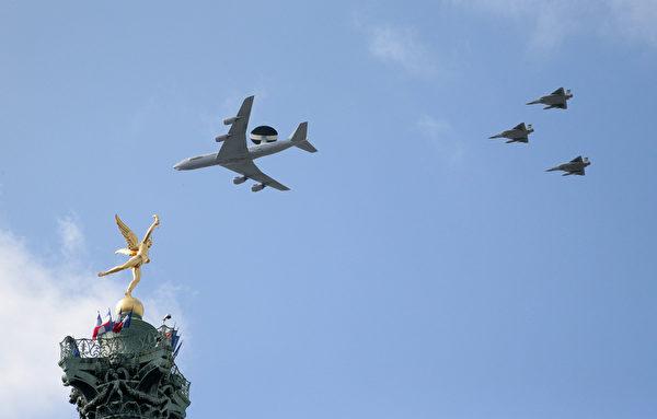 """2015年7月14日,法国国庆日阅兵期间,一架法国空军E3F-预警机跟三架幻影2000战斗机飞过巴黎巴士底广场的七月柱的天使""""自由之神""""上的天空。(JACQUES DEMARTHON/AFP)"""
