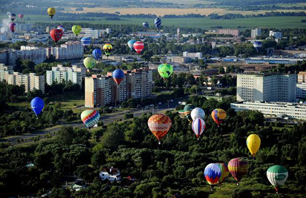 2015年7月18日,在白俄罗举行的第二届国际航空锦标赛,热气球群飞越明斯克郊外的建筑物。共有来自白俄罗斯、乌克兰、俄罗斯、拉脱维亚、立陶宛、波兰、摩尔多瓦和新西兰约70名飞行员参加了比赛。(SERGEI GAPON/AFP)