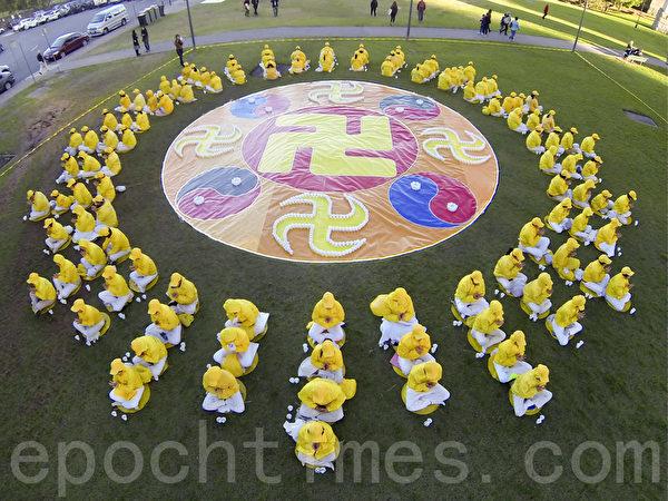 由悉尼法輪功學員和燈光排出的彩色的大法輪和光芒。(周東/大紀元)