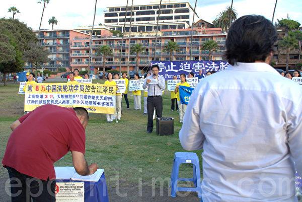 游客在观集会、签名反对活摘器官。(杨婕/大纪元)