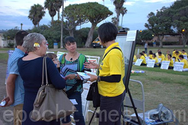 法轮功学员(右一)向游客介绍法轮功和被中共迫害的真相。(杨婕/大纪元)(杨婕/大纪元)