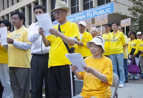 78歲的徐愛華(右,坐者)在先生的陪同下來到集會現場。她曾遭電刑迫害,昏死二天一夜,至今不能行走、不能說話。當晚的集會上,她只能讓先生代替發言。(季媛/大紀元)