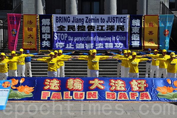 """法轮功学员在""""声援全民控告江泽民""""集会上炼功表演。(唐风/大纪元)"""