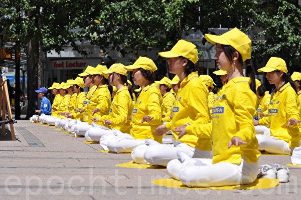 """法轮功学员在""""声援全民控告江泽民""""集会上做功法表演。(唐风/大纪元)"""