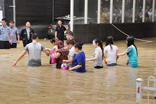 自7月13日以来,中国贵州自西北向东南出现豪雨,引发山洪、城市内涝、山体滑坡等灾害,已造成近20万人受灾。图为贵州省铜仁市,道路淹水,民众涉水而行。 (AFP)