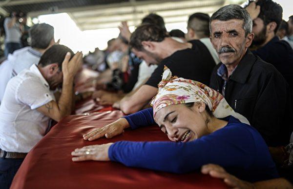 2015年7月21日,前一天土耳其毗邻叙利亚的边界的城镇苏鲁奇一处文化中心传出爆炸案,造成至少31人丧命,是土耳其近年来最致命的恐怖袭击。伊斯兰国承认发动此次自杀式炸弹袭击。图为受害者的葬礼仪式上哀痛逾恒的家属。(BULENT KILIC/AFP/Getty Images)