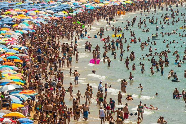 2015年7月22日,西班牙贝尼多姆evante海滩,人们在海滩享受日光浴。西班牙6月涌进2920万游客,已创下观光的新纪录,比2014年同期增长4.2%,观光业是西班牙竞争力最强的项目之一。(David Ramos/Getty Images)