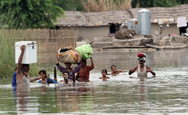 2015年7月23日,巴基斯坦旁遮普省受到洪灾,图为莱亚县一村庄村民涉水通过洪水。(S S MIRZA/AFP/Getty Images)