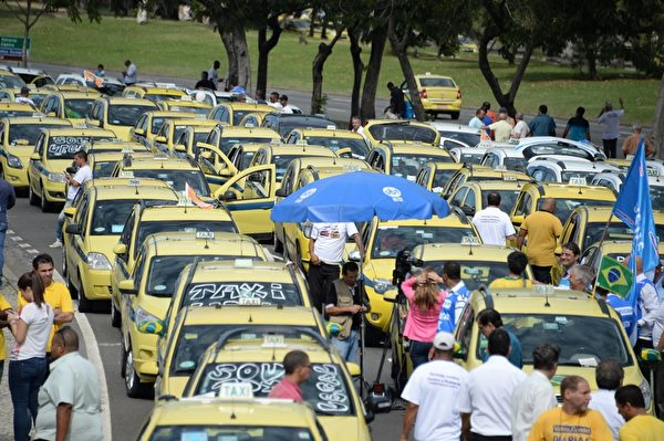 2015年7月24日,里约热内卢,数百名里约热内卢、圣保罗和贝洛奥里藏特的出租车司机排出长达5公里车龙,造成机场交通大打结。以抗议以手机应用程序UBER不法的抢生意。(VANDERLEI ALMEIDA/AFP/Getty Images)