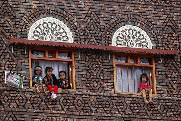 """2015年7月24日,也门首都萨那,孩子坐在窗口看着什叶派激进团体""""青年运动""""的支持者集会抗议以沙特为首的10国联军空袭。(MOHAMMED HUWAIS/AFP/Getty Images)"""