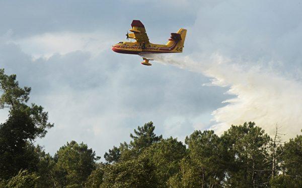 2015年7月24日,一架消防队的森林灭火机试图扑灭法国西南部著名葡萄酒产区波尔多燃起的森林大火。目前,这场火灾已经烧毁将近400公顷松树林。(MEHDI FEDOUACH/AFP/Getty Images)