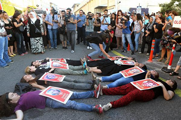 2015年7月23日,土耳其,自7月20日炸弹攻击发生后,数百民众走上伊斯坦布尔街头,抗议伊斯兰国的血腥袭击。图为数名女子躺在地上抱着描绘自杀式炸弹袭击的海报。(ADEM ALTAN/AFP)