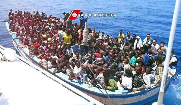 2015年7月24日,由意大利海岸警卫队公布的此视频图片,展示坐在小船等待救援期间的难民。联合国表示,生还者说3艘难民船从利比亚出发,但其中一艘入水下沉,该船载有120人,大部分人被一艘商船和一艘德国海军船只救起,但约有35至40人失踪。(GUARDIA COSTIERA/AFP)