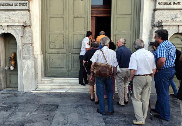 2015年7月20日,人们进入希腊国家银行雅典分行,关闭已达三周的希腊银行终于将在20日恢复局部营业,但仍维持资金管制,每天提款限额仍为60欧元。但实际上众多存户15至18日时就从银行领出了约30亿欧元。(LOUISA GOULIAMAKI/AFP)