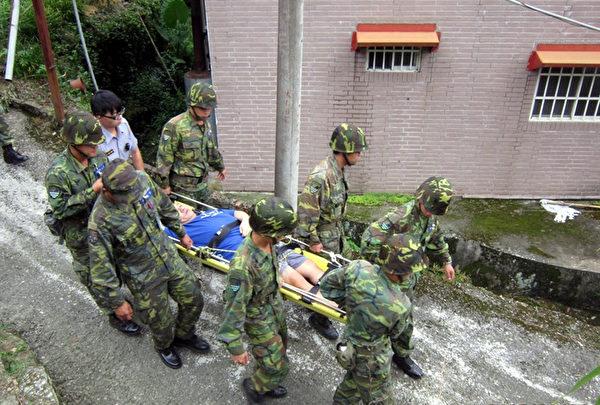 台风苏迪勒来袭,嘉义县预防性撤离低洼地区26位民众,其中1人脚伤行动不便,加上住处低洼,7日由员警、国军联手以担架搬运至安置地点。(警方提供)