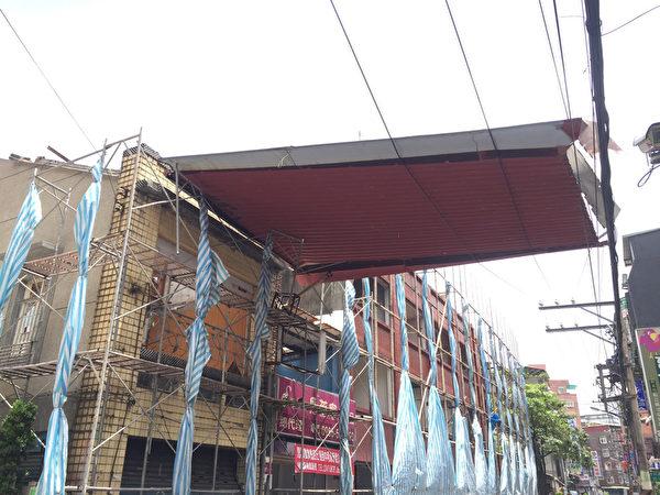 台风苏迪勒来袭,新北市已经有间歇的风雨,中和区景新街一处整修中的民宅,下午发生铁皮屋顶被强风掀起,翻覆后卡在电线上面,工人紧急以吊车移除。(民众提供)