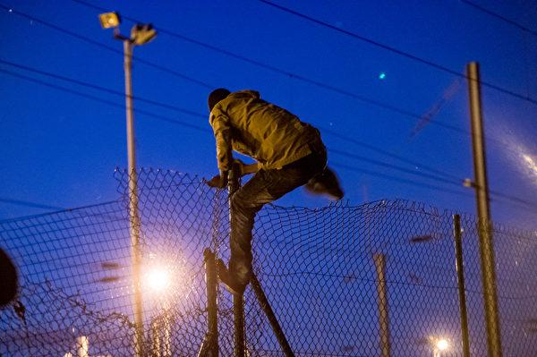 法國北部Frethun,英吉利海峡隧道附近,一名難民越過鐵絲柵欄,準備沿著火車軌道進入法國。 (PHILIPPE HUGUEN/AFP)