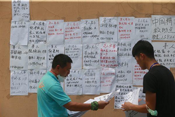 2015年8月14日,天津,民众将失联者的名字贴在安置点外的墙上。(ChinaFotoPress/Getty Images)