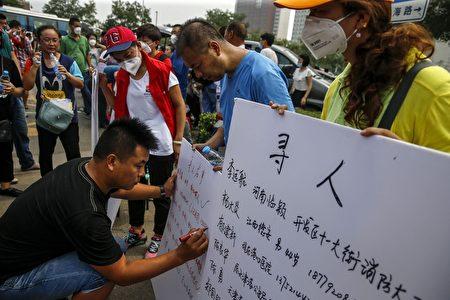 2015年8月14日,天津,民众在展板上写上失联者的名字。(STR/AFP/Getty Images)