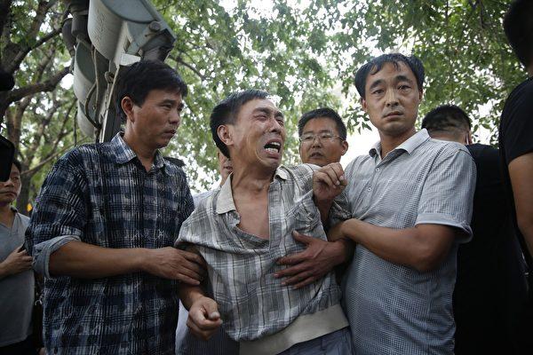 2015年8月16日,天津,抗议现场一名妻子在事故中罹难的男子,情绪悲愤。(STR/AFP/Getty Images)