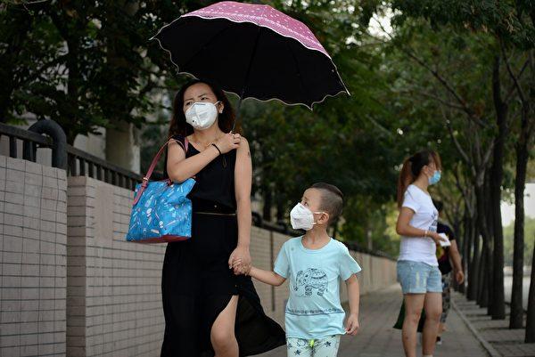 2015年8月16日,天津爆炸事故地点附近的街道上,可见到民众纷纷戴上防护口罩。(WANG ZHAO/AFP/Getty Images)