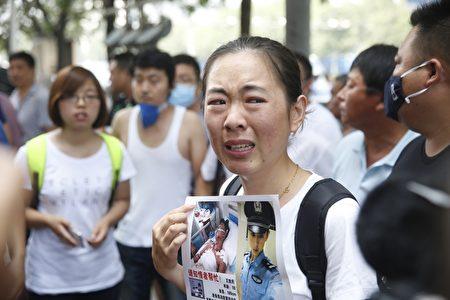 2015年8月16日,天津,新闻发布会的会场外,一名失踪的消防员家属神情悲伤。(STR/AFP/Getty Images)