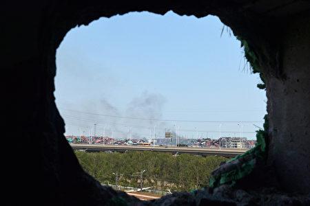 8月18日,天津下了一场大雨,一周前的危险化工品爆炸后的污染问题开始浮现。澳洲昆士兰大学高级研究员的化学专家谢卫国对中共当局的处理生态危机的措施极为忧心。图为,8月16日,从爆炸中击穿的墙壁看远处的爆炸核心区还冒出烟。(AFP PHOTO)